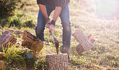 Man in jeans and checkered shirt chopping wood with axe. Action