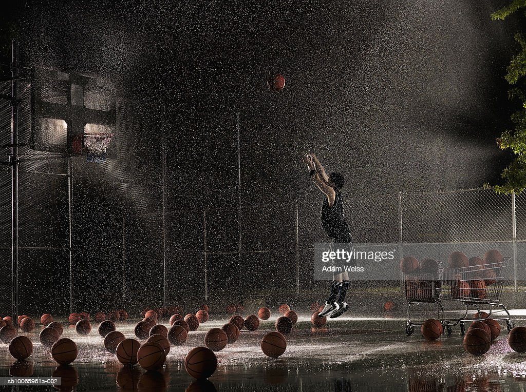 Man shooting basketball at night in rain, side view