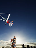 Man shooting layup on outdoor basketball court at sunset