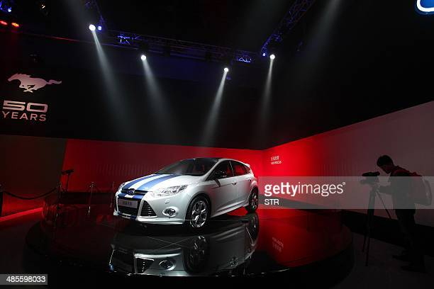 A man shoots video of a new Ford Focus car on the 50 years celebration ceremony of the Ford Mustang in Beijing on April 19 ahead of the 'Auto China...