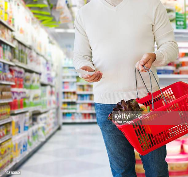 Man shopping, holding list and basket