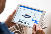 Young man looking at shoes online. Man looking at various shoes options over internet through digital tablet. Casual man makes online shopping at home with digital tablet.