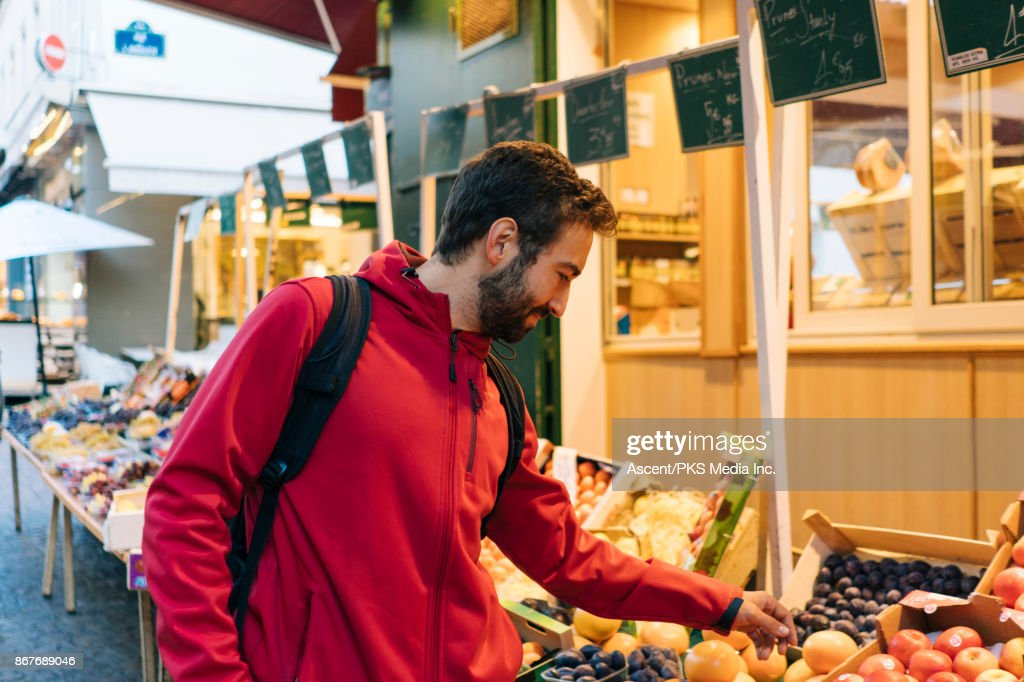 Man shops for produce in outdoor market