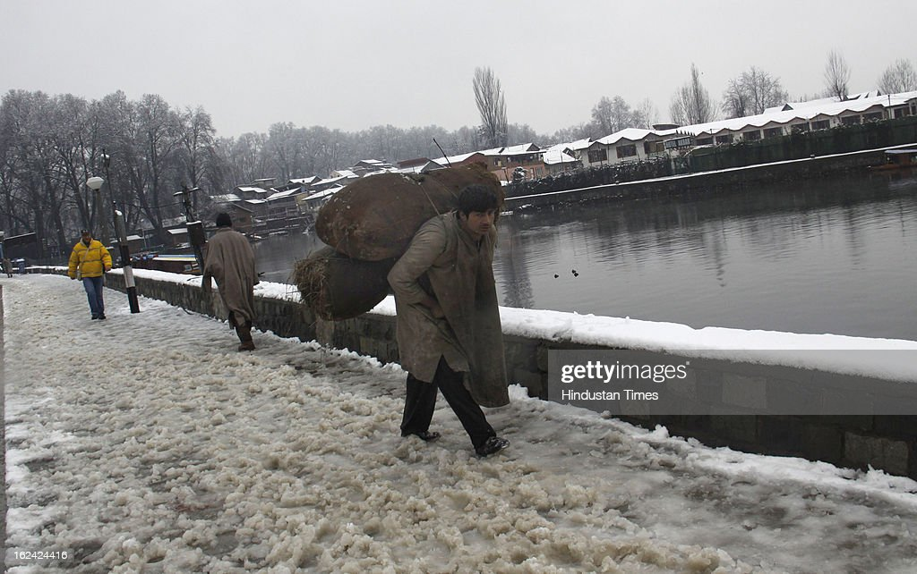 A man shouldering coal bags for the purpose of heating from cold during fresh Snowfall on February 23, 2013 in Srinagar, India. The Jammu-Srinagar National Highway remained closed for the second day on Saturday even as fresh snowfall across Kashmir prompted authorities to issue an avalanche warning in higher reaches of the Valley.
