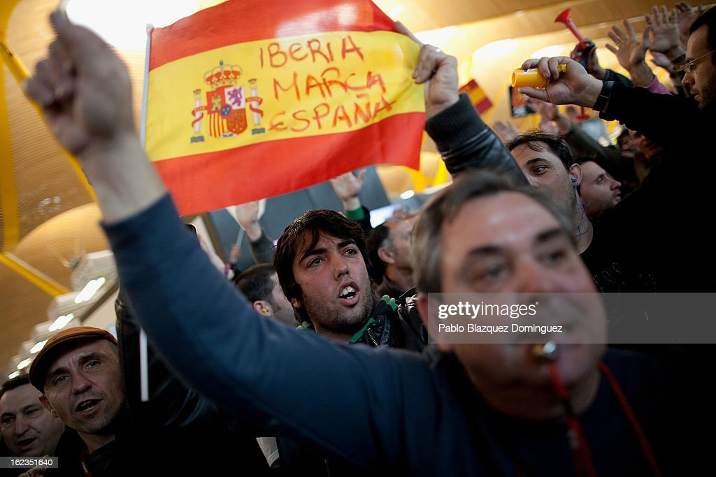 A man shout slogans and holds a Spanish flag reading (Iberia Spain's brand) amid other Spanish Airline Iberia staff during a protest against job cuts at Barajas Airport on February 22, 2013 in Madrid, Spain. Today is the last of a five day strike held by Iberia cabin crew, maintenance workers and ground staff in response to the planned loss of 3,800 jobs. The strike has resulted in the airline having to cancel 400 flights this week with unions planning more five day strikes in the following weeks.