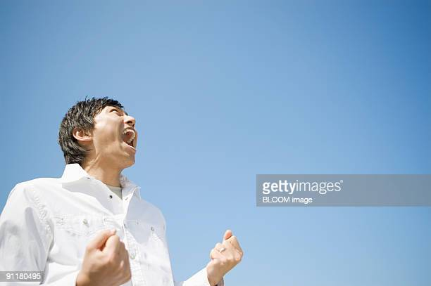 Man shouting, clenching fists, against blue sky