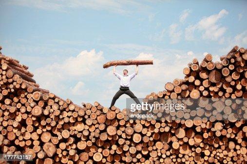 man shouting, lifting heavy log : Stock Photo