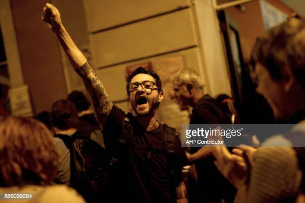 A man shouts as he leaves after overnighting in a wouldbe polling station at a school in Barcelona on October 1 to prevent the police to seal it off...