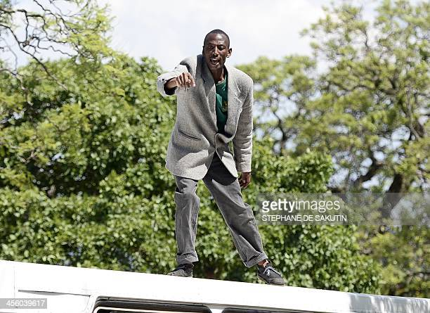 A man shouts as he stands on the top of a packed bus where he climbed after learning that we would not be able to board to pay his respect to South...