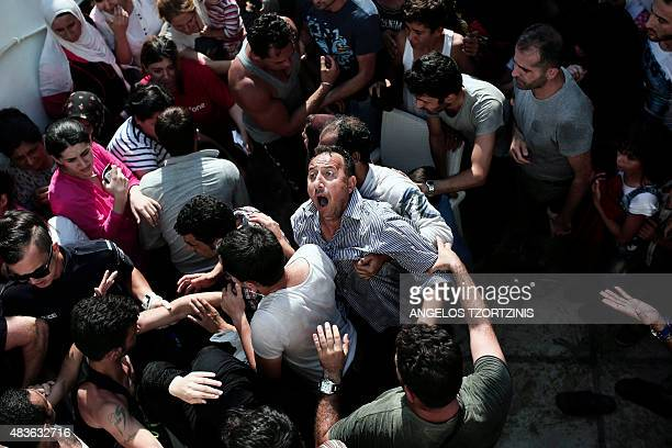 A man shouts as migrants wait to be registered at the stadium on the Greek island of Kos on August 11 2015 Police on the Greek island of Kos hit...