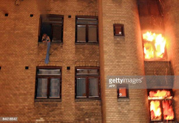 A man shouts for help at a window during a fire in an apartment house in downtown Oslo on December 13 2008 Six people were killed in a fire in an...