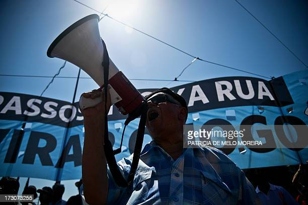 A man shouts slogans with a loudspeaker as he protests with hundreds of workers gathered near the Belem Palace during a general public workers...