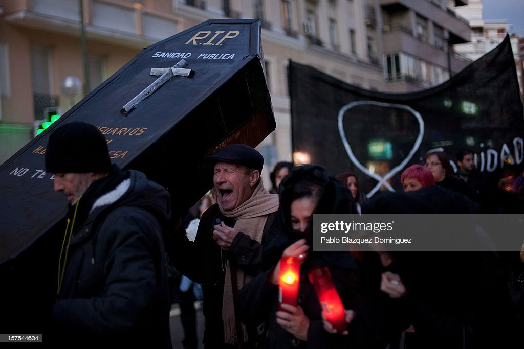 A man shouts while carrying a cardboard coffin amid other health workers during a protest mourning the public health system on December 4, 2012 in Madrid, Spain. Trade unions called for the second 48-hour health workers' strike in the Madrid region, after the regional government announced severe cuts and privatization of medical centers.