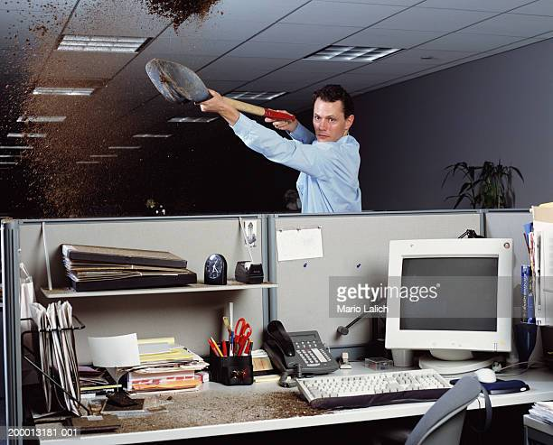 Man shoveling dirt into cubicle