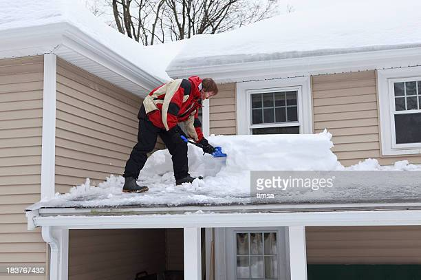 Man shoveling roof with two feet of snow