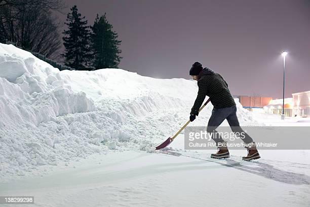Man shoveling snow on road