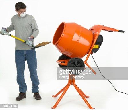 man shovelling mixture into cement mixer stock photo. Black Bedroom Furniture Sets. Home Design Ideas