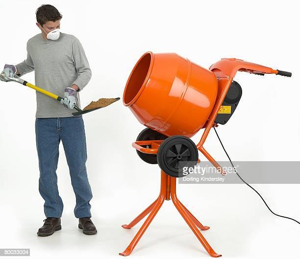 Man shovelling mixture into cement mixer
