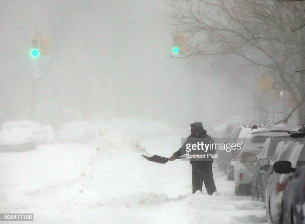 A man shovels his car out in blizzardlike conditions on January 23 2016 in the Brooklyn borough of New York City The Northeast and parts of the South...
