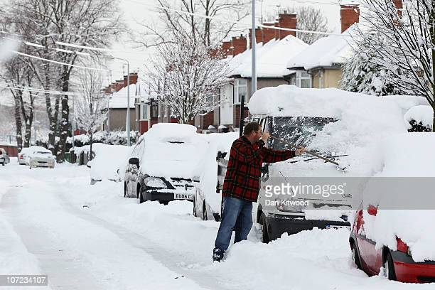 A man shovels snow from his car on a street on December 1 2010 in Goole United Kingdom Freezing weather conditions and heavy snow are continuing to...