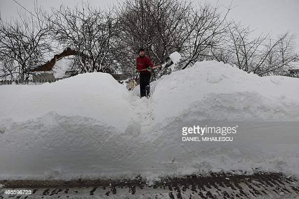 A man shovels snow in front of his home in Smeeni village about 100 kilometers east of Bucharest on January 28 2013 A thick blanket of snow covered...