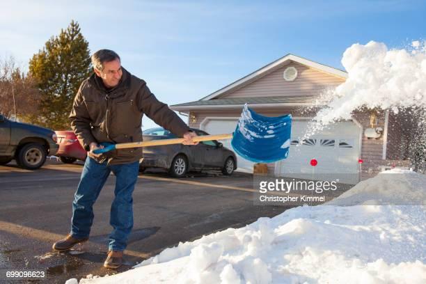 A man Shovels snow in northern Alberta.