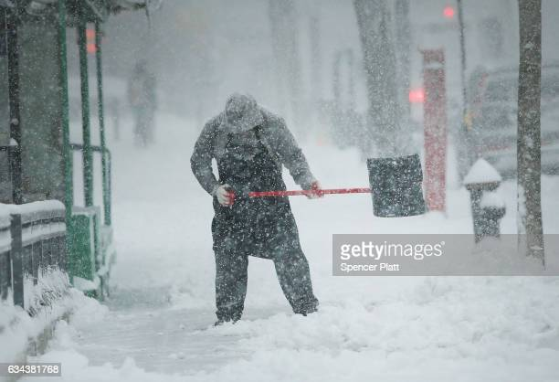 A man shovels snow on February 9 2017 in the Brooklyn borough of New York City A major winter storm warning is forecast from Pennsylvania to Maine...