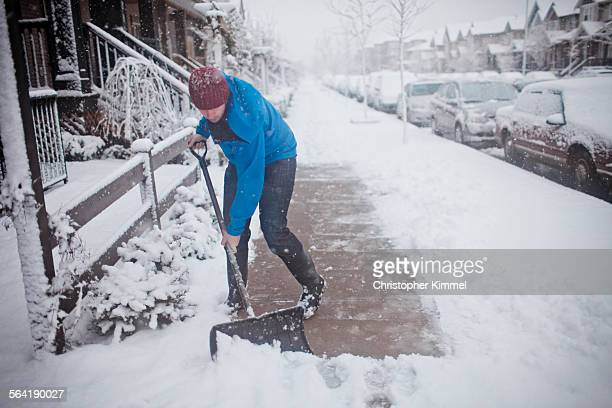 A man shovels the sidewalk outside of his suburban house.