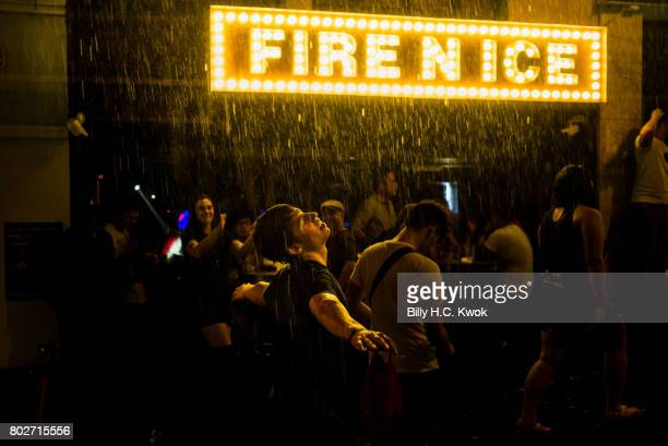 A man showers in the rain at Lan Kwai Fong a famous clubs street in Hong Kong on June 17 2017 in Hong Kong Hong Kong Hong Kong is marking 20 years...