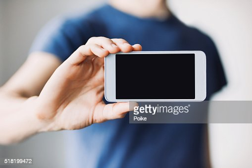 Man showing a blank phone screen : Stock Photo