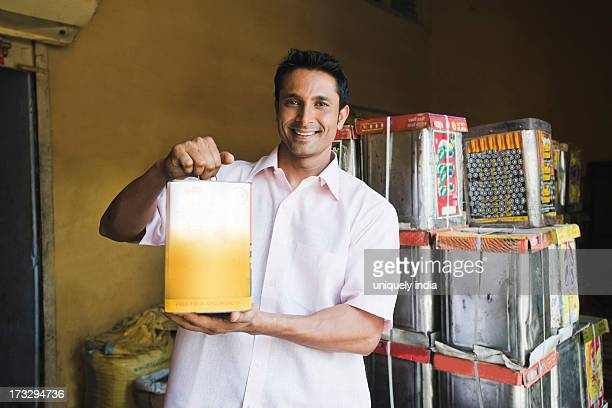 Man showing a canister of edible oil in a store, Sohna, Gurgaon, Haryana, India