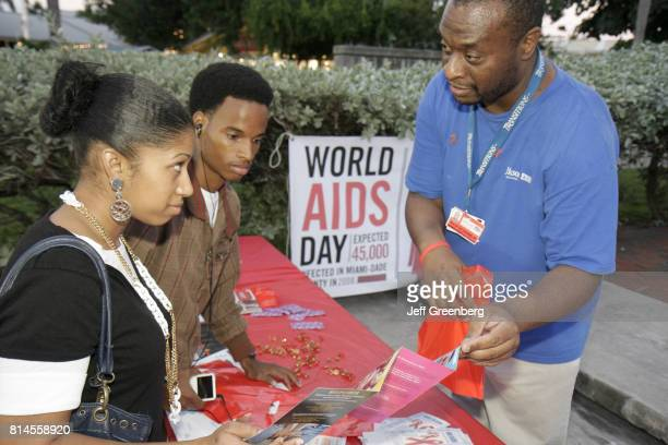 A man showing a couple sexually transmitted disease brochures for World AIDs Day