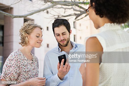 Man showing cell phone to women : Foto de stock