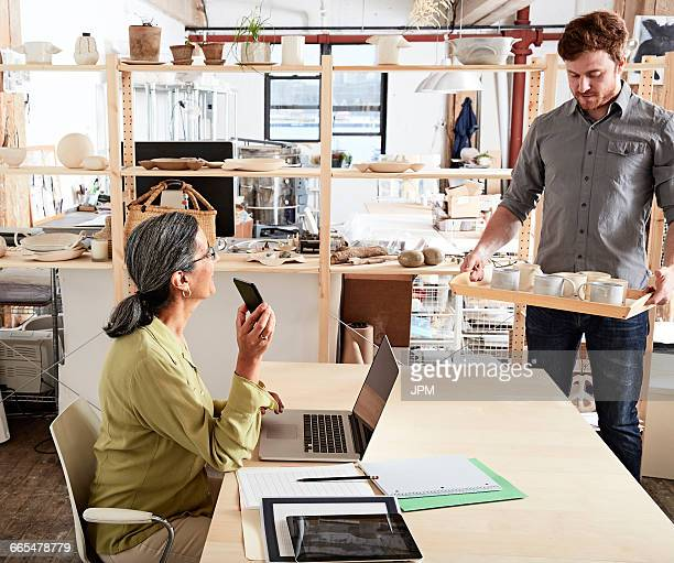 Man showing colleague tray of ceramics