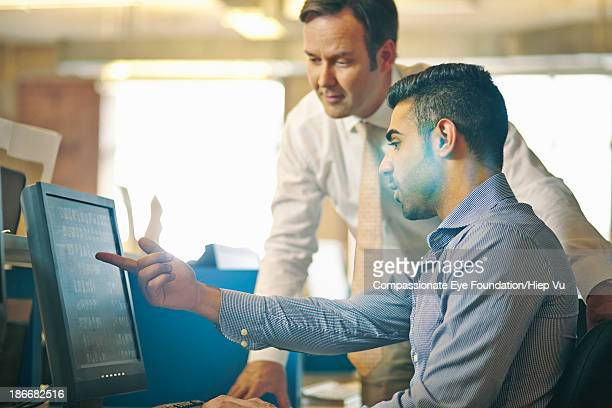 Man showing colleague work on computer screen