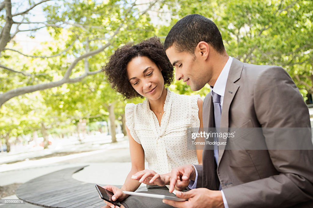 Man showing digital tablet to woman : Stock-Foto