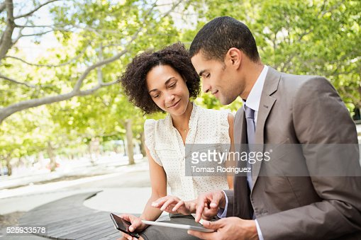 Man showing digital tablet to woman : Stock Photo