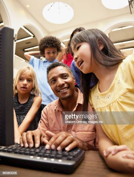 Man showing group of children how to use computer