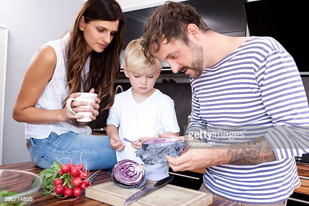 Man showing his little son red cabbage in the kitchen
