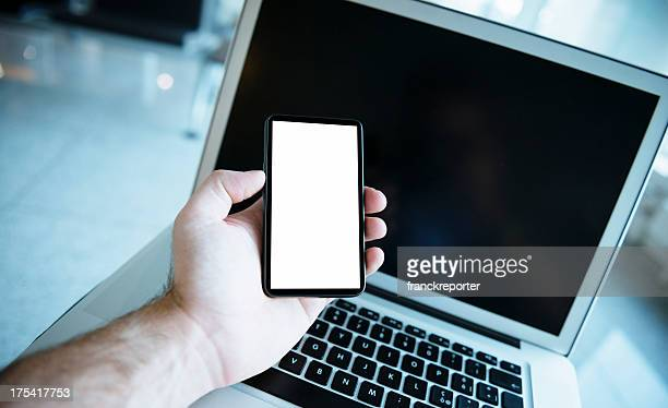 Man Showing new smartphone with blank screen and laptop