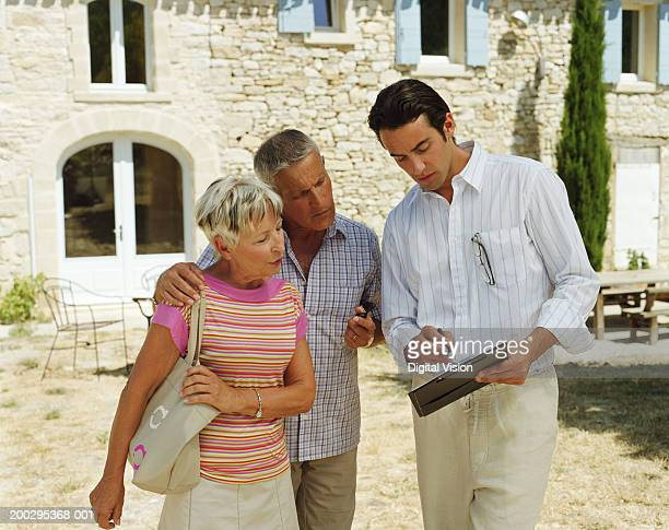 Man showing paperwork to couple outside house
