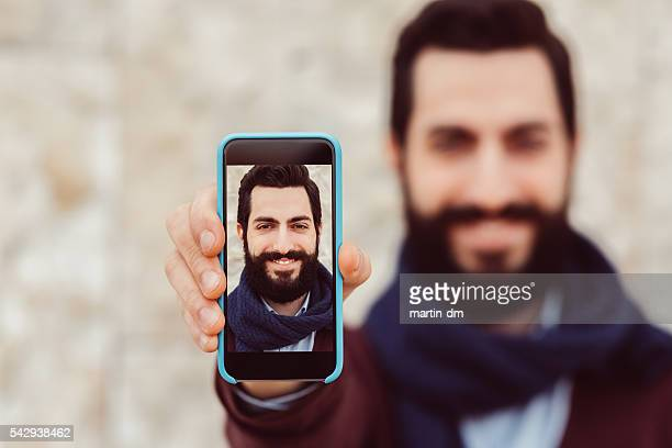 Man showing self photo on smartphone