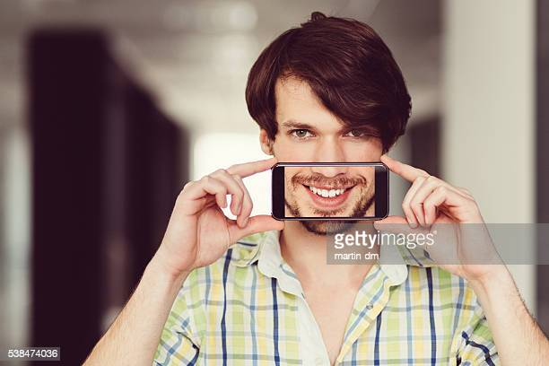 Man showing white toothy smile on smartphone
