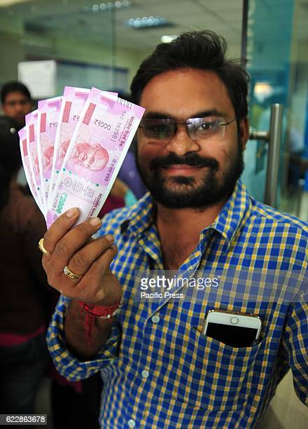 A man shows 2000 rs currency note after change his 500 and 1000 currency notes in Allahabad