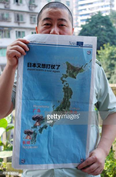 A man shows a fullpage advertisement under the title 'Japan wants a war again' on local newspaper the Chongqing Youth Daily in southwest China's...
