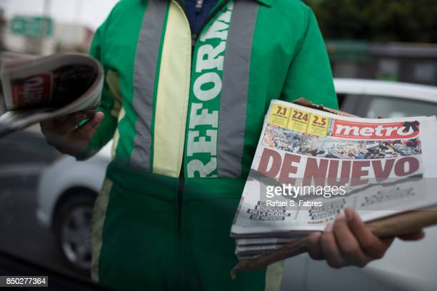 A man shows a local newspaper with the headline that translates in English to 'Again' refering to Tuesday's earthquake is shown on September 20 2017...