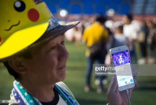 A man shows a Mewtwo a character from Nintendo Co's Pokemon Go augmented reality game to the media during the Pokemon Go Stadium event at Yokohama...