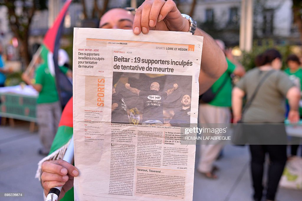 A man shows a newspaper reading 'Beitar 19 supporters charged with attempted murder' while pro Palestinians demonstrators gather in front of the city...