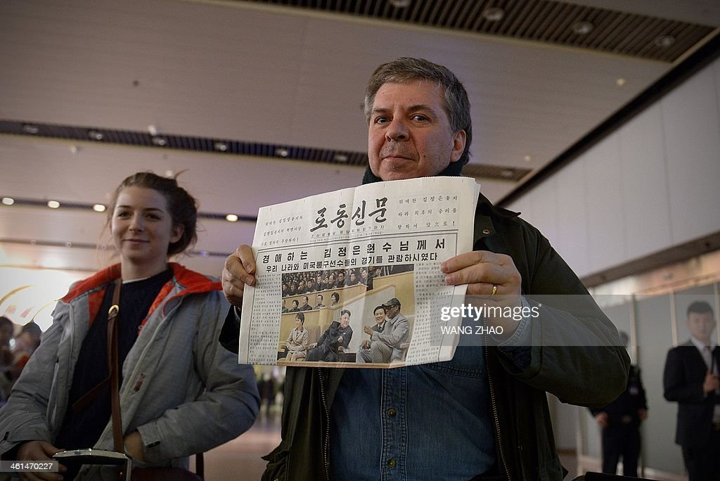 A man shows a North korean newspaper to the media as he arrives at Beijing's international airport from North Korea on January 9, 2014. Former US basketball star Dennis Rodman sang 'Happy birthday to you!' to North Korean leader Kim Jong-Un in Pyongyang on January 8, before joining a game with fellow players to mark the event. AFP PHOTO / WANG ZHAO