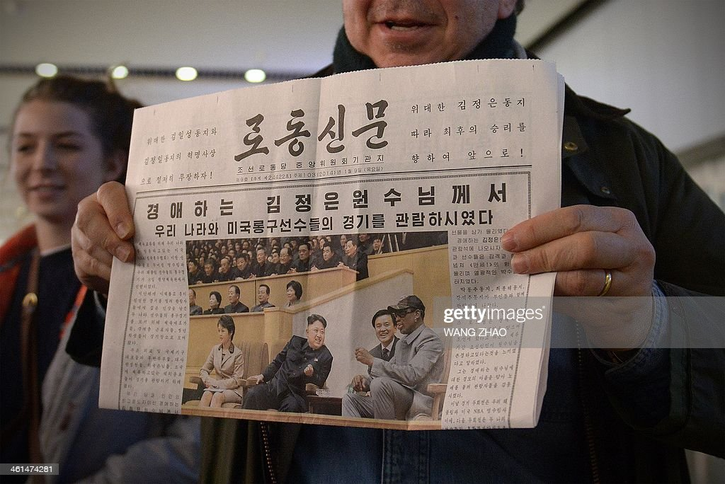 A man shows a North korean newspaper to the media as he arrives at Beijing's international airport from North Korea on January 9, 2014. Former US basketball star Dennis Rodman sang 'Happy birthday to you!' to North Korean leader Kim Jong-Un in Pyongyang on January 8, before joining a game with fellow players to mark the event.